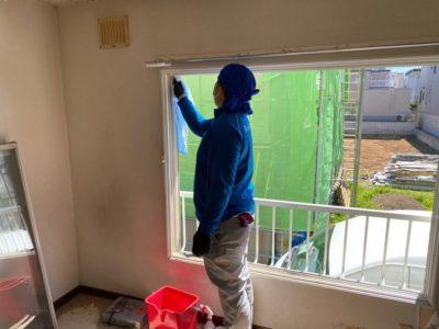 窓を清掃中の小川店長